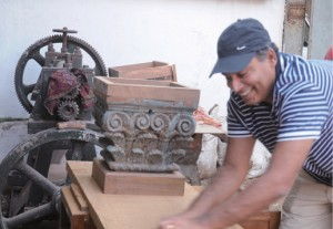 Hard labour: Sujjain Talwar brings an old piece of furniture back to life.